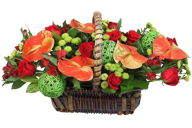 籐のかごの中の花の花束、赤いアンスリウム、スプレー菊、赤いバラ。植物相構成、フラワーアレンジメント、白い背景の上の孤立した画像。