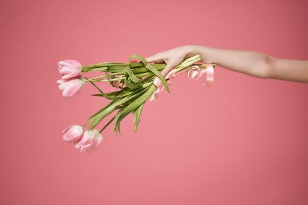 手に花束とギフトロマンス夏ピンクの背景