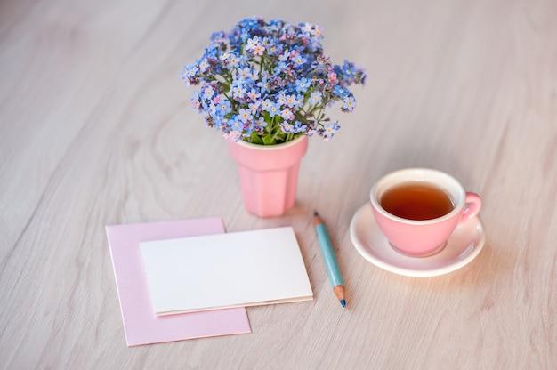 Букет цветов незабудки на столе с чашкой чая и открыткой для текста поздравления.