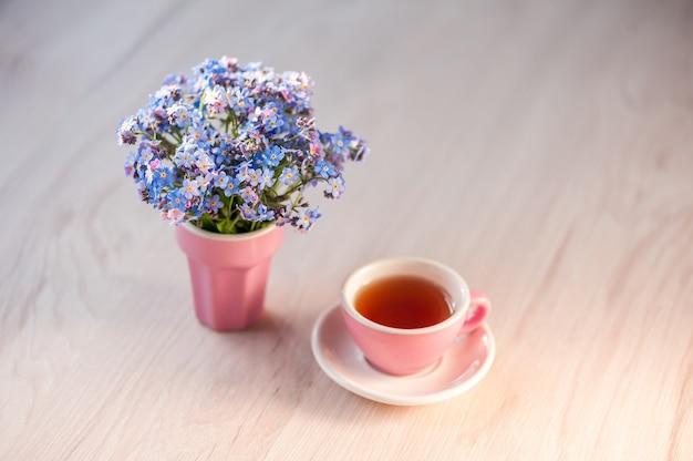 お茶とテーブルの上のワスレナグサの花の花束。休日の背景、コピースペース、ソフトフォーカス。母の日、誕生日のコンセプト。