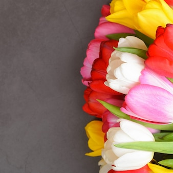 Букет свежих, ярких, разноцветных тюльпанов на серой поверхности