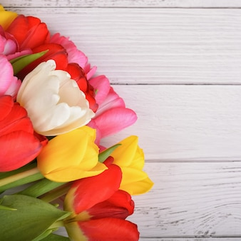 Букет из свежих, ярких, разноцветных тюльпанов на белых деревянных досках.