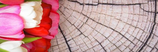 Букет свежих, ярких, разноцветных тюльпанов на деревянных досках.