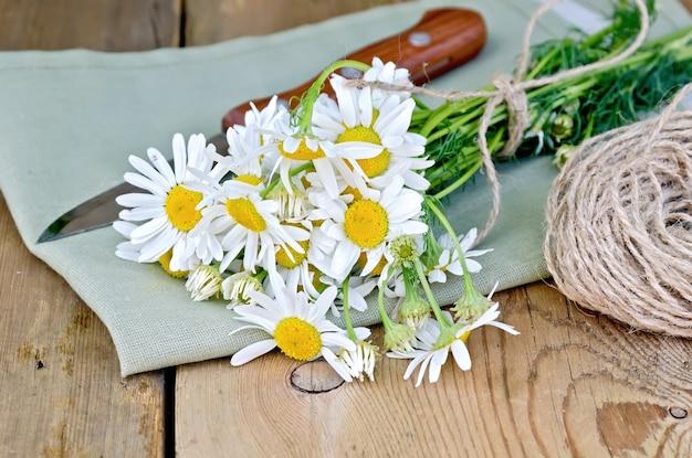 나무 판의 배경에 냅킨에 감기와 칼 신선한 카모마일 꽃의 꽃다발