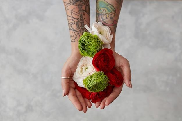 신선한 꽃 꽃다발, 회색 배경에 꽃을 들고 손에 문신을 한 소녀. 인사말 카드 평면도의 개념