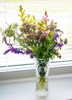 빛으로 가득 찬 흰색 창에 신선한 야생화 꽃다발