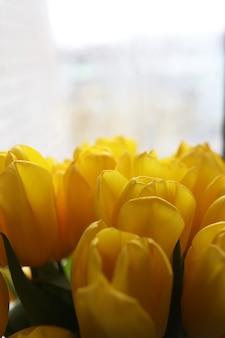 窓の近くのテーブルの上に花瓶に新鮮な黄色のチューリップの花束