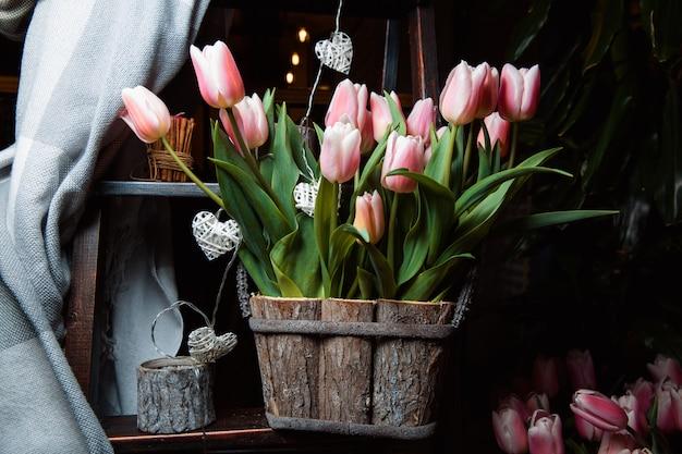 木製の箱に優しくピンクのチューリップの花束。家の装飾。