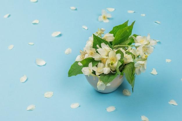青い背景にジャスミンの花と散らばった花びらの花束。