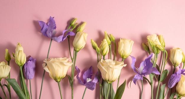 ピンクの壁に淡黄色のトルコギキョウとライラッククレマチスの花束。コピースペース。高品質の写真