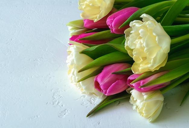 明るい黄色のテリーとピンクのチューリップの花束が明るい背景に横たわっています