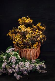 黒い木製の背景に薬草の花束-咲くミントとセントジョンズワート。