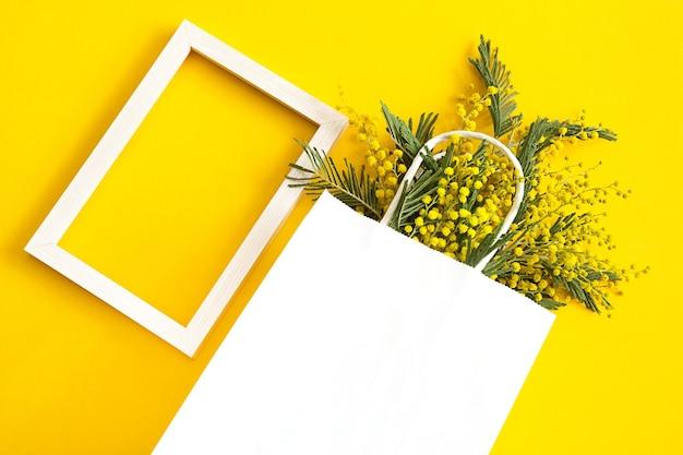 白いモックアップギフトバッグに入ったミモザの花束。春の買い物