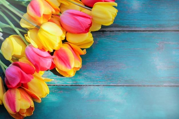 青緑色の木製のテーブルの上に色とりどりのチューリップの花束があります。春の気分とロマンチックな気分の概念。上からの眺め。