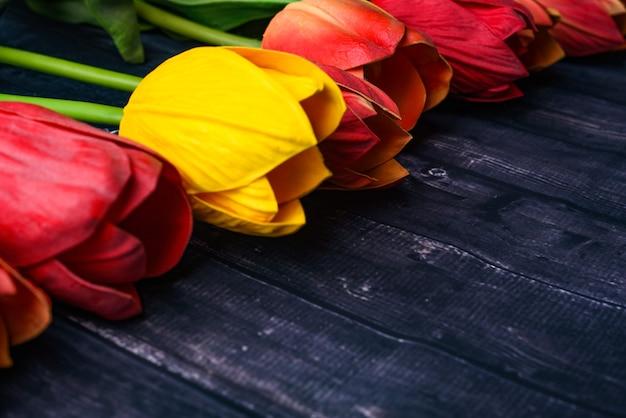 素朴な木製のテーブルの上にオレンジと黄色のチューリップの花束
