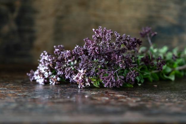 木製のテーブルにオレガノの花の花束。コピースペース