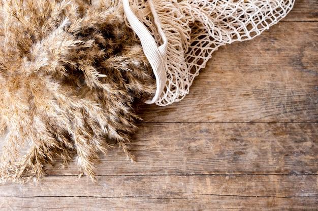 Букет пампасных трав лежит в авоське на деревянном столе.