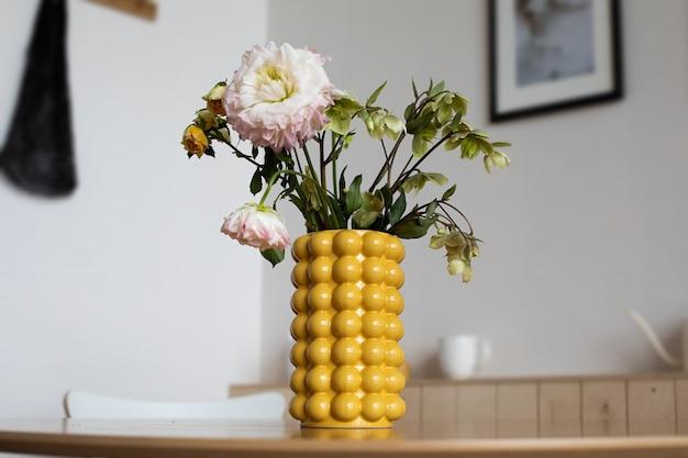 黄色のセラミックデザイナー花瓶に牡丹の花束。キッチンインテリア。それはテーブルの上です 。