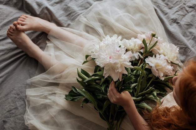 子供の手のベッドの上の牡丹の花束。