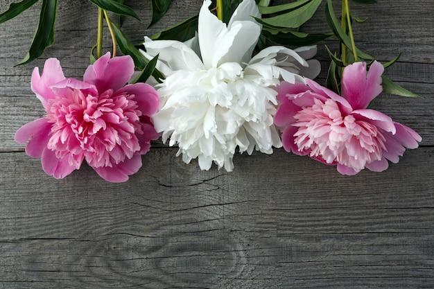 テクスチャーのある古いボードの背景にピンクと白の咲く牡丹の花の花束。