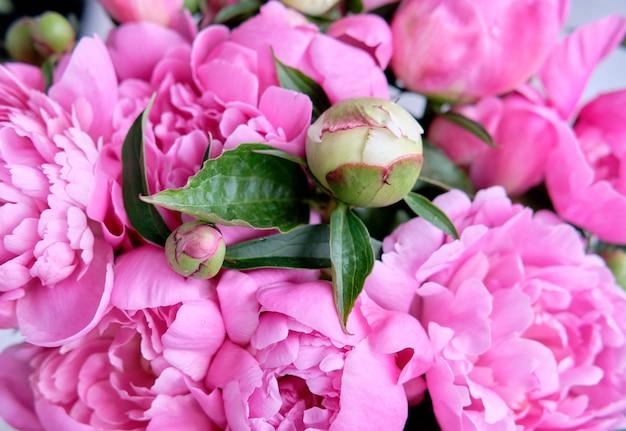 Букет розовых малиновых пионов крупным планом лежит на деревянном столе