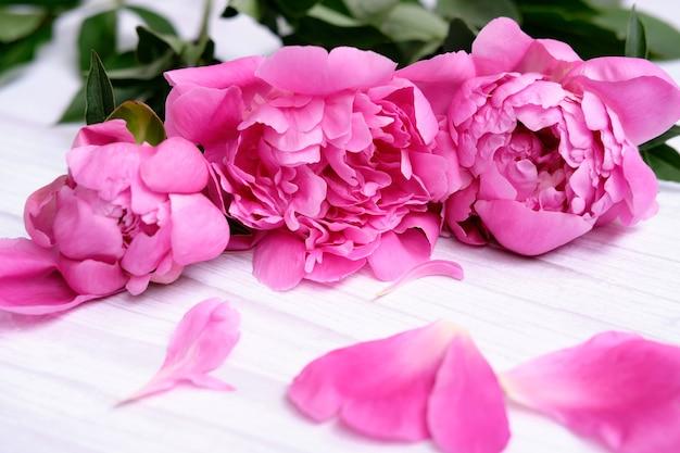 Букет из розовых цветочных пионов и лепестков на светлом деревянном