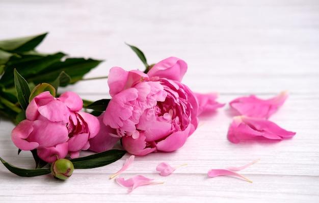 Букет из розовых пионов и лепестков на светлом деревянном