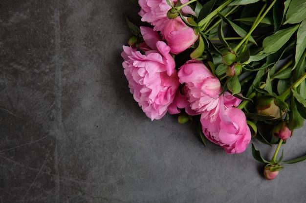 Букет розовых пионов в линию на темной деревянной поверхности.