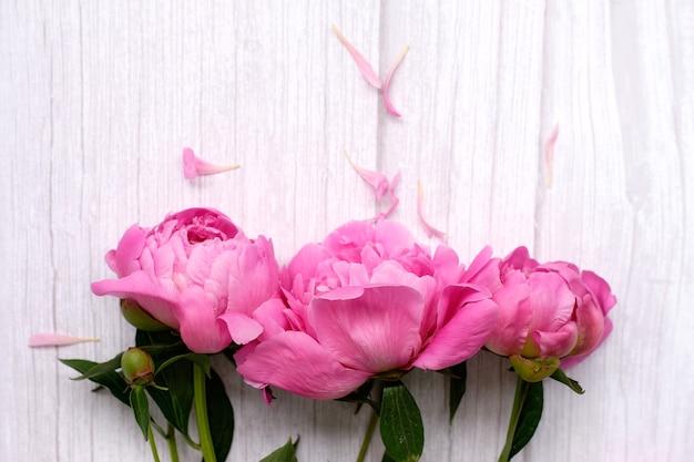 Букет розовых пионов на ярком деревянном цветке