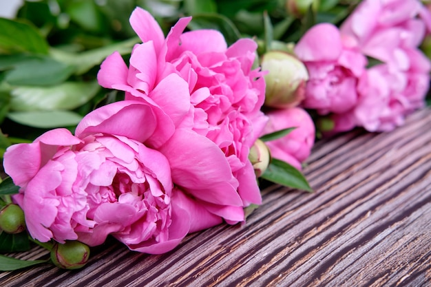 Букет розовых пионов на темном деревянном цветке