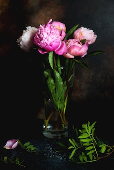 Букет из розовых пионов стоит на темном фоне. креативная картинка для обоев и интерьера.