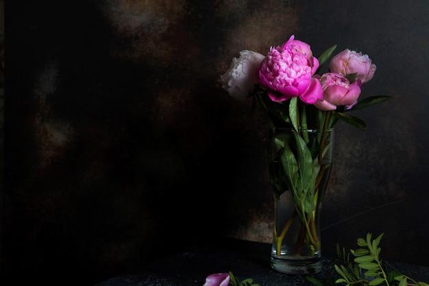 暗い背景にピンクの牡丹の花束が立っています。壁紙とインテリアのクリエイティブな写真。
