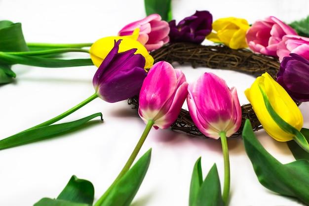 Букет из розовых, фиолетовых и желтых тюльпанов на белом фоне