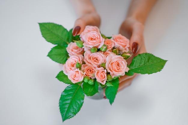 근접 촬영 위에서 잘 손질된 여성의 손이 들고 있는 분홍색 장미 꽃다발