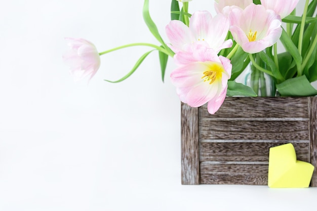 木製の箱と白地に黄色の紙のハートのピンクのチューリップの花束。