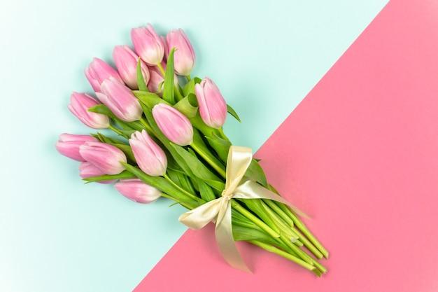 파란색과 분홍색 배경 봄 꽃에 리본으로 묶인 분홍색 튤립 꽃다발