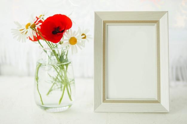 ガラスの花瓶にポピーとデイジーの花束と窓際の白いテーブルの上の空のフォトフレーム。 mokap。