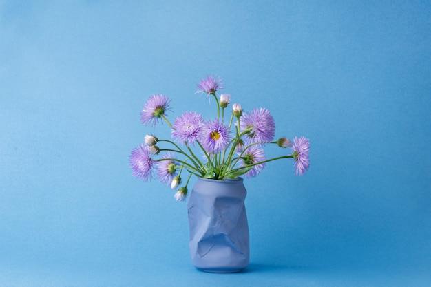Букет фиолетовых цветов ромашки в вазе из-под банки с газировкой