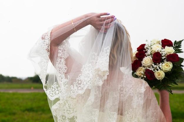 신부의 손에 있는 빨간색과 흰색 장미 꽃다발. 하얀 드레스를 입고 웨딩 부케를 든 베일을 입은 소녀. 행복의 미소, 진정한 사랑, 결혼