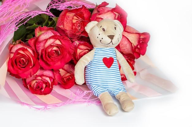 Букет красных роз в подарочной бумажной упаковке и мягкий игрушечный мишка с вышитым сердечком. валентина концепция