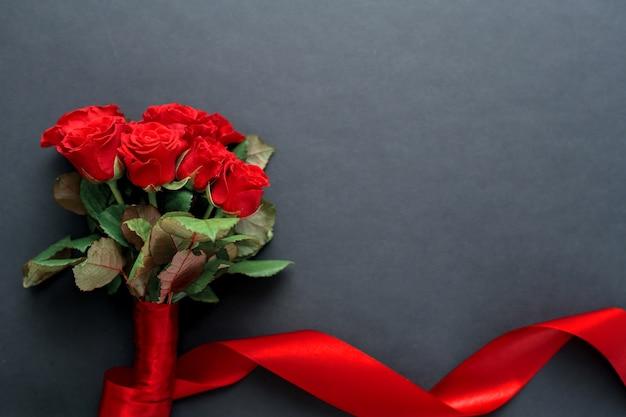 검정색 배경에 아름다운 리본이 달린 빨간 장미 꽃다발