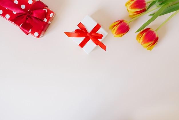コピースペースのある白いテーブルに赤い春の花のチューリップと赤いギフトボックスの花束。バレンタインデー