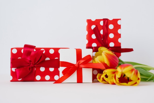Букет из красных весенних цветов тюльпанов и красных подарочных коробок.