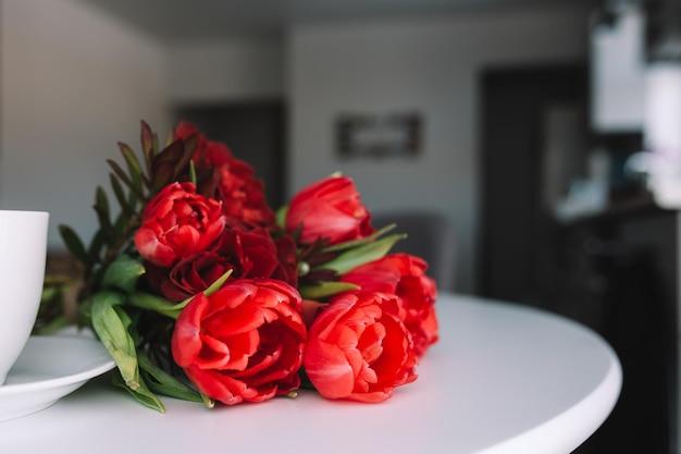 テーブルの上の赤いチューリップの花束と白い一杯のコーヒー。グリーティングカードのコンセプト。