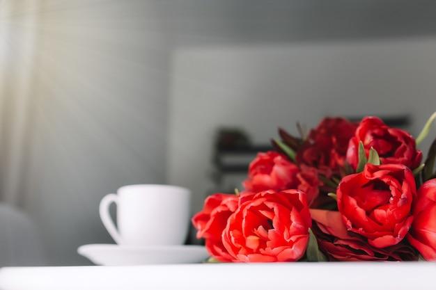 Букет красных тюльпанов на столе и белая чашка кофе.