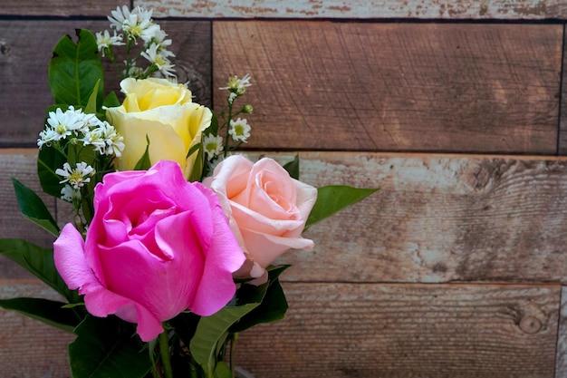 木製の背景にバラの花の花束