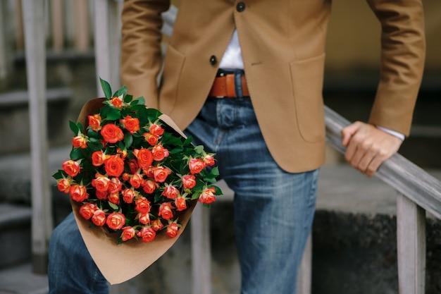 男性の手にバラの花束。