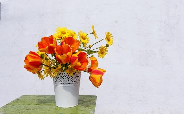明るい背景に白い花瓶に春の花の花束。木製スタンド。