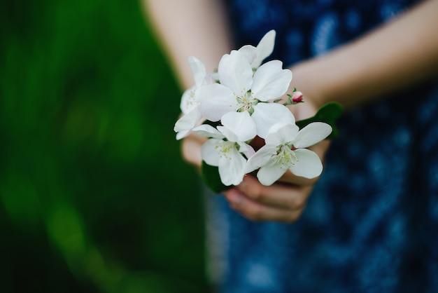 女の子の手の中の春の花の花束。春の公園で咲くリンゴの木。ソフトフォーカス。閉じる。