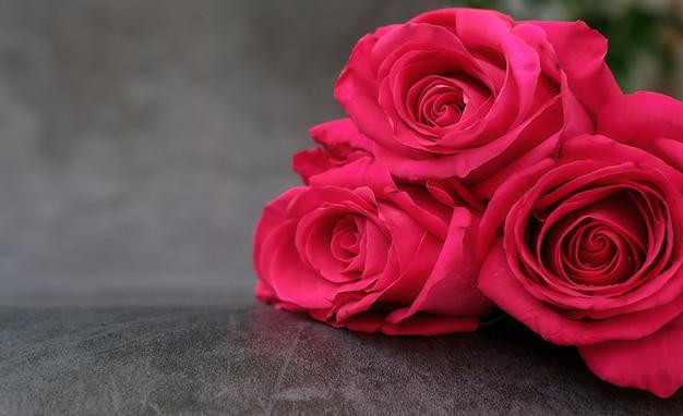 Букет из трех красных роз на сером с местом для текста